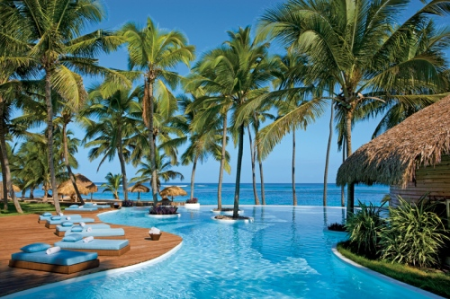 The Infinity Pool at Zoetry Agua Punta Cana looks out to the Calm Ocean and Beach